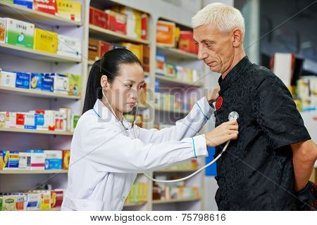 chinese pharmacist chemist woman examining heartbeat of customer in china pharmacy drugstore