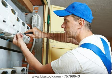 electrician engineer worker assembling fuseboard equipment meter in room