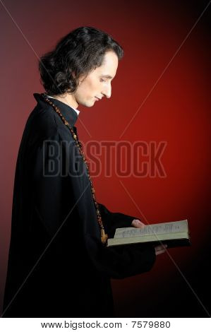 Conceptual Portrait Of Praying Priest With Wooden Cross Reading Holy Bible. Red Background