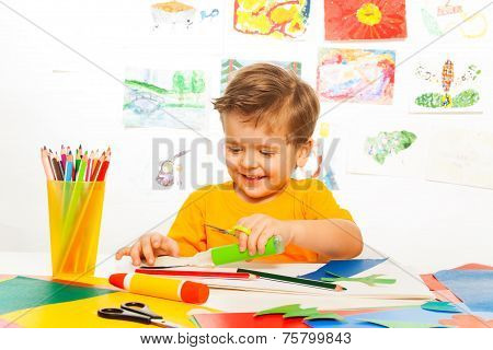 Happy small boy crafts with scissors, paper, glue