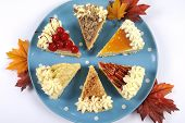 foto of happy thanksgiving  - Thanksgiving apple pecan cherry caramel pumpkin spice and chocolate cream cheesecake pie on blue polka dot platter against a white table with autumn fall leaves - JPG