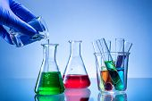 stock photo of flask  - Laboratory equipment bottles flasks with color liquid hand poured - JPG