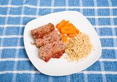 picture of meatloaf  - Homemade meatloaf sliced on a plate with brown rice and sliced carrots - JPG