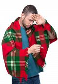 pic of freezing temperatures  - Young man is holding thermometer in hand covered with plaid blanket - JPG