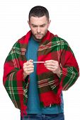 foto of freezing temperatures  - Young man is holding thermometer in hand covered with plaid blanket - JPG