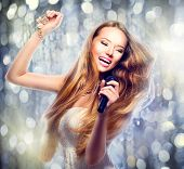 stock photo of singer  - Beauty model girl with a microphone singing and dancing over holiday glowing background - JPG