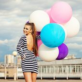 foto of latex woman  - Happy young woman with colorful latex balloons outdoor - JPG