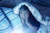 picture of horrifying  - Horrified Boy Watching Film At Night under the cover - JPG
