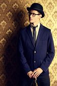 picture of bowler  - Portrait of a handsome young man in elegant suit and bowler hat posing over vintage background - JPG