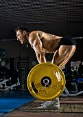 stock photo of snatch  - very brawny guy bodybuilder execute exercise deadlift with weight in gym - JPG