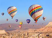 stock photo of balloon  - Hot air balloon flying over rock landscape at Cappadocia Turkey - JPG