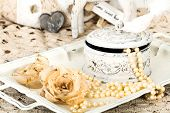 picture of shabby chic  - antique jewelry box with pearls on ladies dressing table with shabby chic pearl necklace and lace  - JPG