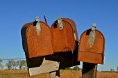 foto of mailbox  - A cluster of three rusty mailboxes stand together  in a ghost town - JPG