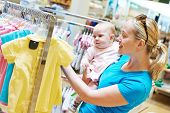 stock photo of apparel  - woman choosing children apparel with little baby child girl on hands in clothing shop supermarket - JPG