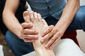 stock photo of fingers legs  - Masseur making a traditional chinese foot massage to adult leg and foot - JPG
