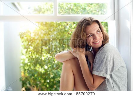 Happy Mid Adult Woman Sitting By Window At Home