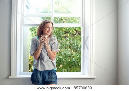 Happy Woman Standing By Window Smiling With Cup Of Coffee