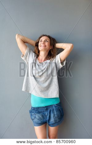 Cute Mid Adult Woman Smiling With Hands Behind Head