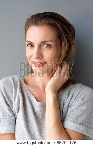 Lovely Mid Adult Woman Smiling With Hand In Hair