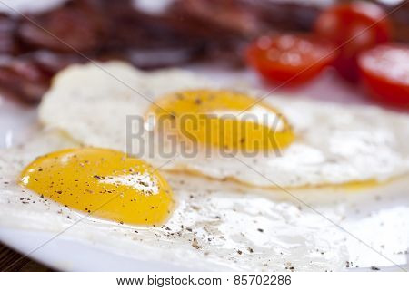 Delicious Fried Egg With Spices, Bacon, Croutons And Tomatoes On A White Plate.