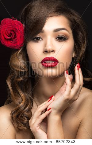 Beautiful girl in the Spanish way of Carmen with red lips and a rose in her hair.