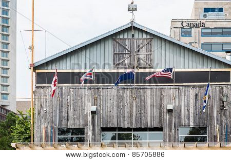 American And Canadian Flags On Old Wood Building