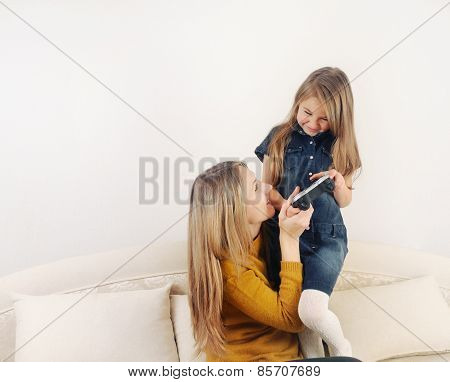 Little Girl With Her Mother Playing Tv Video Game Device On The Sofa At Home, Technology Concept