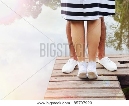 Romantic Couple Kissing On The Pier Near Lake In Summer Day