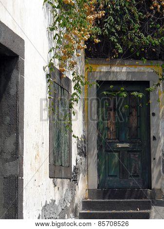 Rotting wooden door with peeling green paint