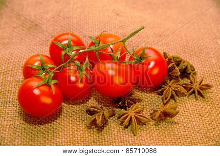 Red Cherry Tomats And Star Anise Fruits On Old Cloth