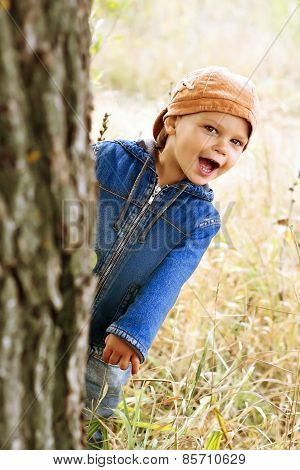 Little Boy Peeping From Behind A Tree.