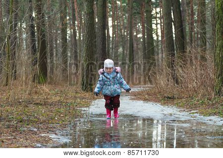 Little girl walking on icy puddle
