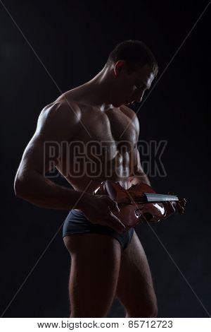 Bodybuilder Holding A Violin.