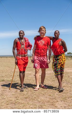 MASAI MARA,KENYA, AFRICA- FEB 12 Masai men in traditional clothes and European tourists