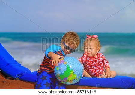 kids looking at globe on tropical beach