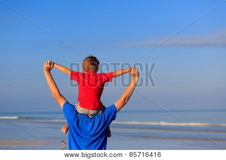 happy father and son playing on sea beach
