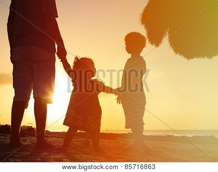 father and two kids walking at sunset