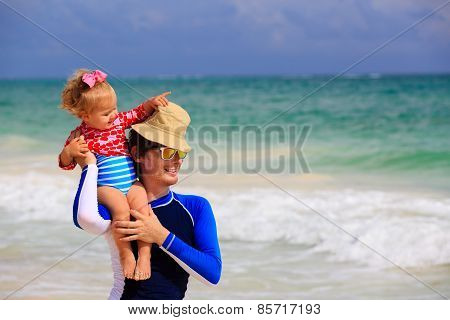 father and little daughter fun on the beach