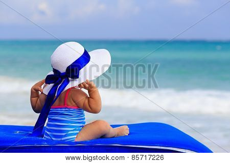 rear view of little girl in big hat on summer beach