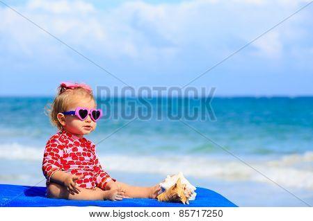 cute little girl  with seashells on the beach