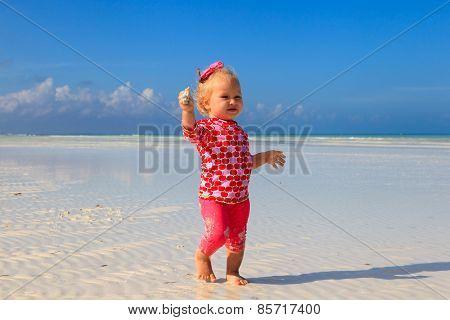 cute little girl walking on summer beach