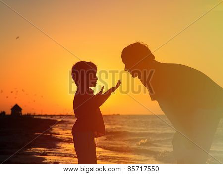 father and little son talking at sunset