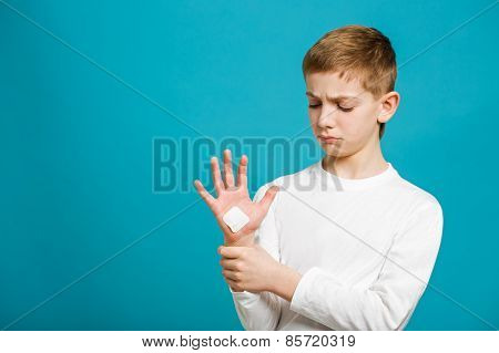 Sad Boy Looking At White Adhesive Plaster On His Hand