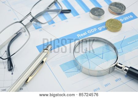 Magnifying Glass, Pen And Glasses On Financial Chart And Graph