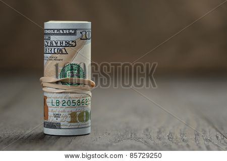roll of new style hundred dollar bills stand on wooden table