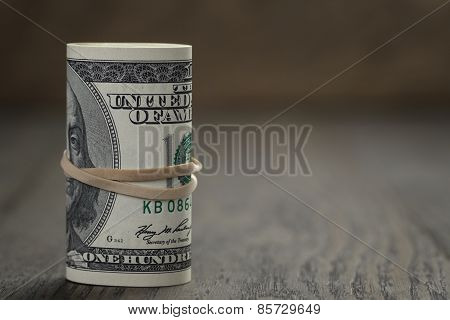 roll of old style hundred dollar bills stand on wooden table