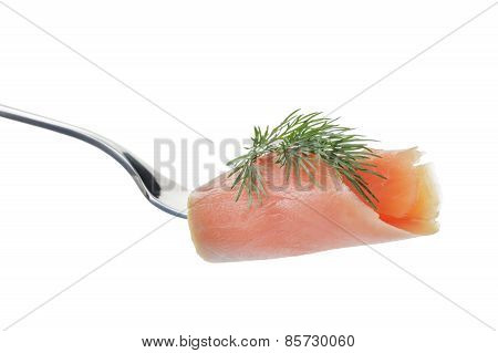 rolled curred salmon on fork with dill isolated