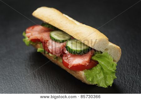 sandwich with salmon and vegetables on slate background