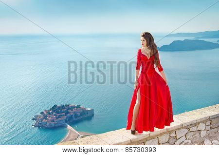 Beautiful Fashion Girl Model In Gorgeous Red Dress Over The Sea, Blue Sky. Sveti Stefan, Montenegro.