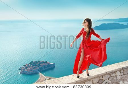 Beautiful Girl In Blowing Red Dress Flying. Fashion Gorgeous Model Over Blue Sky. Free. Freedom Conc